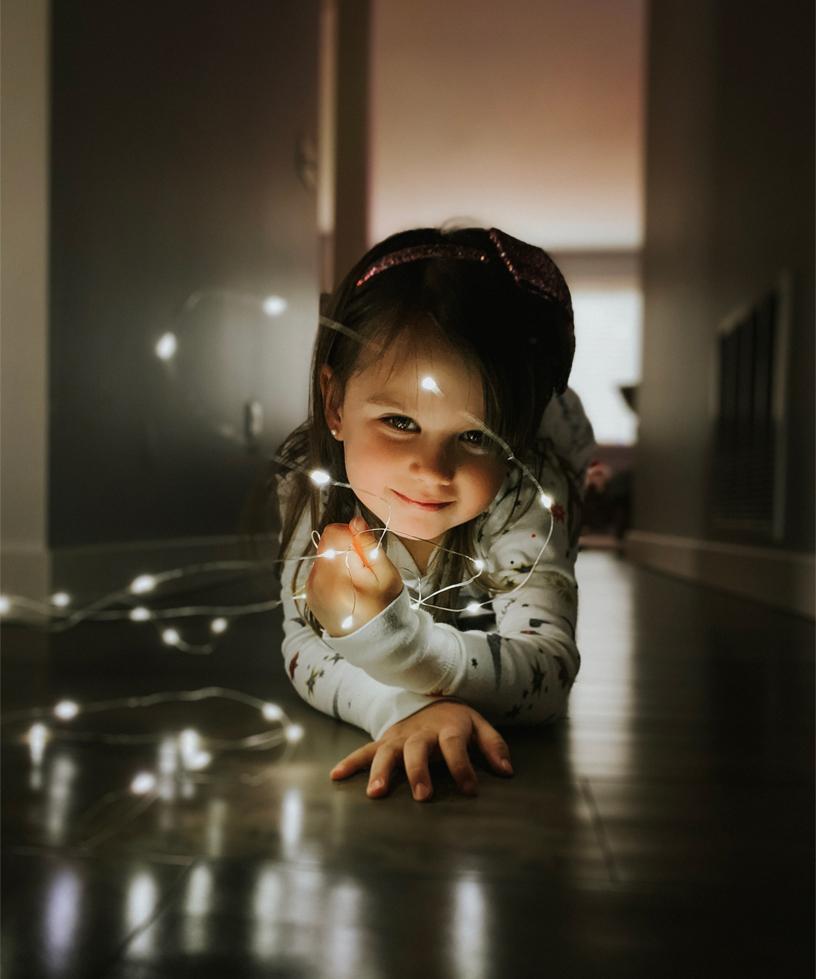 Shot on iPhone holiday Little girl with string lights 12192018 big.jpg.large  Apple publie des photos des utilisateurs prises avec liPhone XS et XR pour les fêtes de fin dannée
